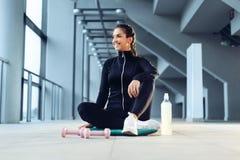 Femme de sport s'asseyant et se reposant après séance d'entraînement ou exercice dans le gymnase de forme physique photo libre de droits