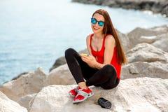 Femme de sport sur la plage rocheuse Image libre de droits
