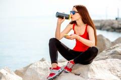 Femme de sport sur la plage rocheuse Photos stock