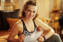 Femme de sports avec le plan de forme physique de bâtiment de presse-papiers et de stylo photos stock