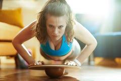 Femme de sports dans la maison moderne faisant des pompes utilisant le panneau d'?quilibre photo libre de droits