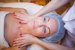 Femme de station thermale de cosmétologie faisant le massage facial Images libres de droits
