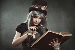 Femme de Steampunk avec le livre et la lentille Images stock
