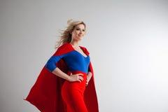 Femme de super héros Jeune et belle blonde dans l'image du superheroine dans l'élevage rouge de cap Photographie stock