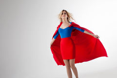 Femme de super héros Jeune et belle blonde dans l'image du superheroine dans l'élevage rouge de cap Images libres de droits