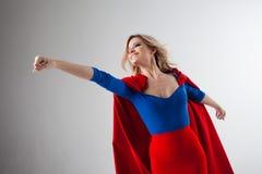 Femme de super héros Jeune et belle blonde dans l'image du superheroine dans l'élevage rouge de cap Photos stock