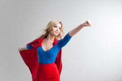 Femme de super héros Jeune et belle blonde dans l'image du superheroine dans l'élevage rouge de cap Images stock