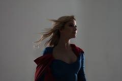 Femme de super héros Jeune et belle blonde dans l'image du superheroine dans l'élevage rouge de cap Image libre de droits