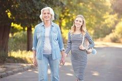 Femme de support tenant des mains avec la fille enceinte en parc Image stock