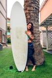 Femme de surfer avec le bikini et le wetsuit tenant la planche de surf photo stock