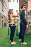 Femme de surfer avec le wetsuit fermant d'homme de bikini Photo stock