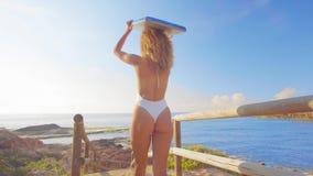 Femme de surfer sur le voyage de vacances de plage allant surfant la marche avec la planche de surf au coucher du soleil sur la p banque de vidéos