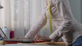 Femme de tailleur choisissant les couleurs de conception sur l'ordinateur portable, coordination d'ordre avec le client banque de vidéos
