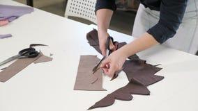 Femme de tailleur coupant des détails des travaux de tissu en travaillant des affaires d'atelier banque de vidéos