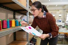 Femme de tailleur de jeunes regardant le fil de bobine de couleur Photographie stock libre de droits