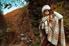 Femme de touristes avec la tasse de thermos de voyage examinant la distance image stock