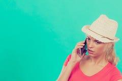 Femme de touristes avec le chapeau du soleil parlant au téléphone Image stock