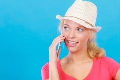 Femme de touristes avec le chapeau du soleil parlant au téléphone Photo stock