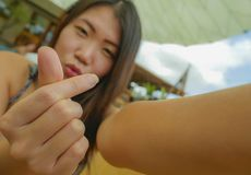 Femme de touristes coréenne asiatique heureuse souriant tenant le téléphone portable ou appareil-photo prenant la photo de selfie images stock