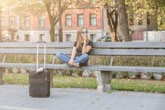 Femme de touristes de pensée, s'asseyant sur le banc en parc images stock