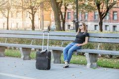 Femme de touristes de pensée, s'asseyant sur le banc en parc photographie stock libre de droits