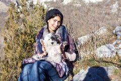 Femme de touristes s'asseyant sur le dessus de la montagne, étreignant son chien blanc Photo libre de droits