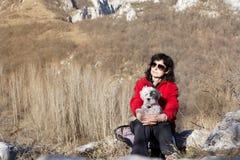 Femme de touristes s'asseyant sur le dessus de la montagne, étreignant son chien blanc Image stock
