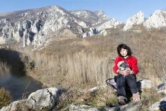 Femme de touristes s'asseyant sur le dessus de la montagne, étreignant son chien blanc Photos libres de droits