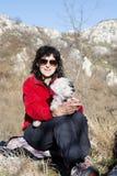 Femme de touristes s'asseyant sur le dessus de la montagne, étreignant son chien blanc Photographie stock