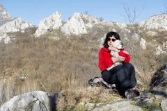 Femme de touristes s'asseyant sur le dessus de la montagne, étreignant son chien blanc Photos stock