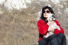 Femme de touristes s'asseyant sur le dessus de la montagne, étreignant son chien blanc Image libre de droits