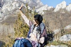Femme de touristes s'asseyant sur le dessus de la montagne, étreignant son chien et ondulation blancs Photo libre de droits