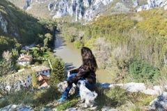 Femme de touristes s'asseyant sur le dessus de la montagne d'automne, appréciant la vue Photo libre de droits