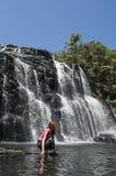 Femme de touristes s'asseyant sur les roches près de la belle cascade étonnante photo stock