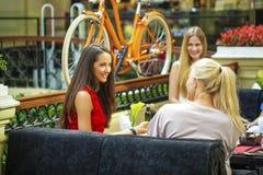 Femme de trois amies s'asseyant à une table dans le café Photo stock