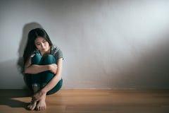 Femme de trouble bipolaire de dépression s'asseyant sur le plancher image stock