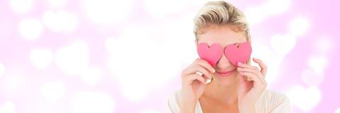 Femme de valentines tenant des coeurs au-dessus des yeux avec le fond de coeurs d'amour Photographie stock