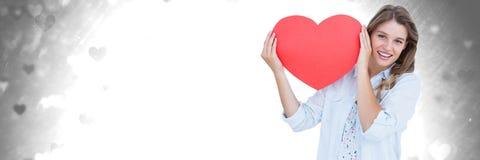 Femme de valentines tenant le coeur avec le fond de coeurs d'amour Photographie stock