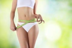 Femme de ventre avec le mètre sur le fond vert Photos stock