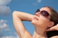 Femme de visage avec des lunettes de soleil sur le ciel photos stock