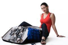 Femme inquiétée à côté de sa valise ouverte Photo stock