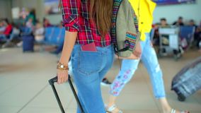 Femme de voyage de jeunes dans la chemise occasionnelle avec les bagages marchant dans le terminal d'aéroport moderne Plan rappro banque de vidéos