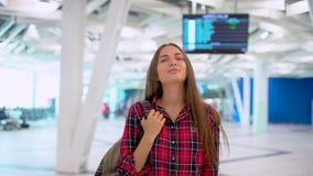Femme de voyage de jeunes dans la chemise occasionnelle avec les bagages marchant dans le terminal d'aéroport moderne tourisme de banque de vidéos