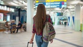 Femme de voyage de jeunes dans la chemise occasionnelle avec les bagages marchant dans le terminal d'aéroport moderne Vue du dos  banque de vidéos
