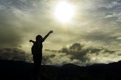Femme de voyageur avec le sac à dos appréciant le coucher du soleil sur la montagne maximale, lo Image libre de droits