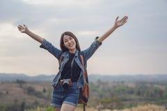 Femme de voyageur avec le sac à dos avec des bras augmentés photographie stock