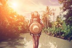 Femme de voyageur avec le sac à dos se tenant près de la grande rivière tropicale Photo libre de droits