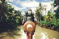 Femme de voyageur avec le sac à dos se tenant près de la grande rivière tropicale au jour ensoleillé Image libre de droits