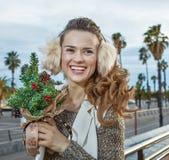 Femme de voyageur avec un peu d'arbre de Noël regardant dans les Di Image libre de droits