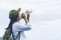 Femme de voyageur buvant avec le sac à dos appréciant le coucher du soleil sur la crête MOIS Image libre de droits
